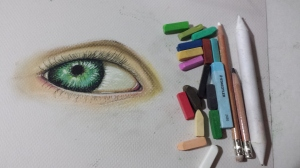 Materials used to paint an eye in soft pastels